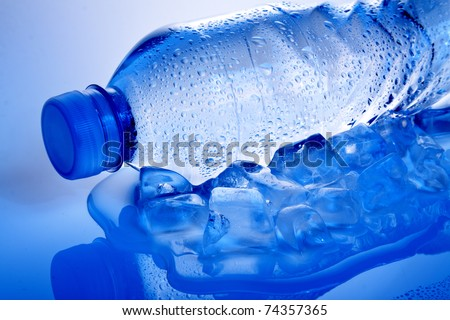 water bottle lying on its side on ice with droplets on it, shot in cool blue tone - stock photo