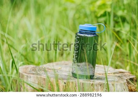 Water bottle on wood  with summer scene background - stock photo