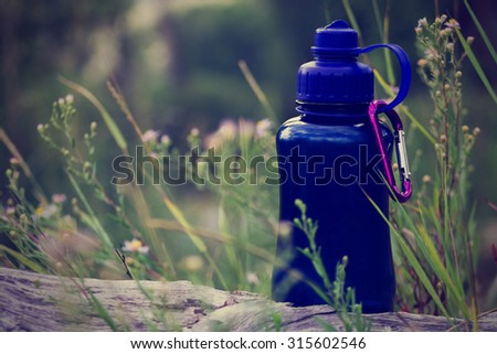 water bottle sitting on a log while on a hike with a retro instagram toned filter with a shallow depth of field