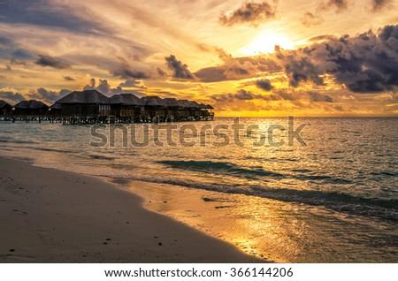 Water bungalows at sunset. Maldive Islands - stock photo