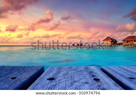 Water bungalows with beautiful twilight sky and sea after sunset in Maldives. Long Exposure. - stock photo