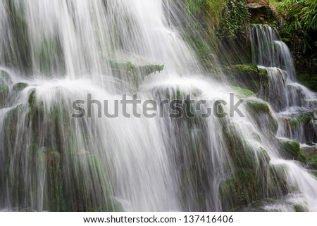 Water cascading over mossy rocks with long exposure blur - stock photo