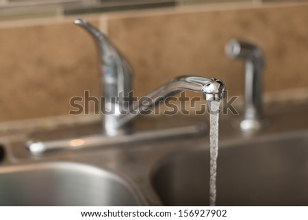 Water coming out of a faucet. View is a 3/4 view with shallow depth of field on the water coming out. - stock photo