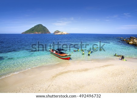 water confident snorkeling with blue sky and colorful boat