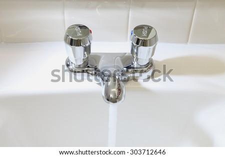 Water conserving Bathroom sink fixture - stock photo