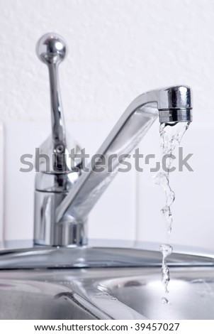 Water dribbling from a leaking faucet on the kitchen sink. - stock photo
