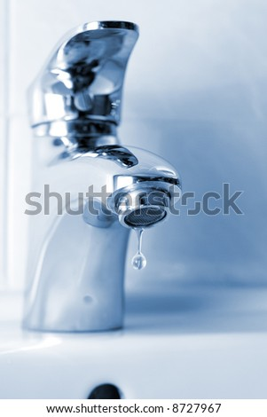 Water dripping from a faucet, closeup