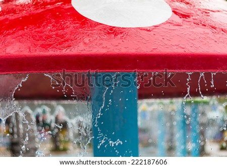 Water dripping from a toy Umbrellas  The mushroom shaped - stock photo