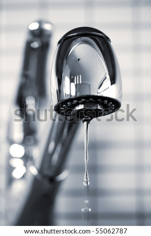 Water dripping from stainless steel kitchen faucet - stock photo