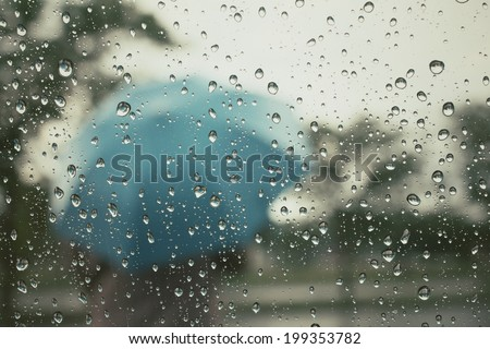 Water drop and blurred umbrella  - stock photo