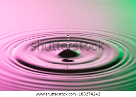Water drop close up with concentric ripples on colourful pink and green surface