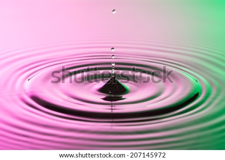 Water drop close up with concentric ripples on colourful pink surface