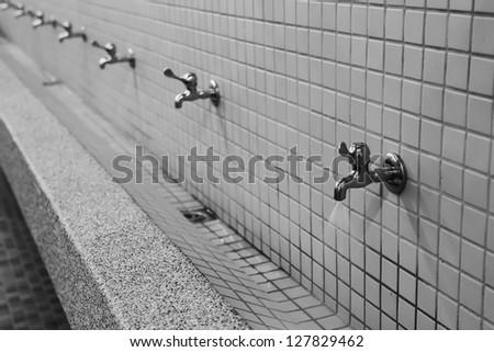 water drop falling down a metal tap - stock photo