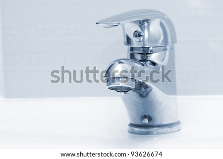 Water drop falling form a faucet in a blue bathroom - stock photo