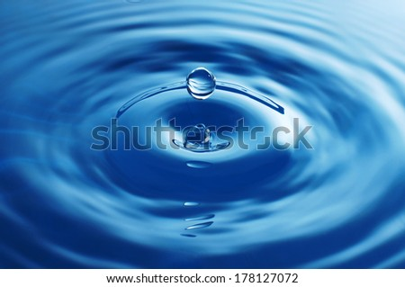 Water drop falling into the water - stock photo