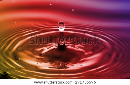 Water drop falling into water making a droplet splash - stock photo