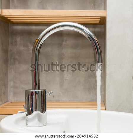Water drop from faucet in bathroom. - stock photo