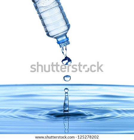 water drop from water bottle on to pool of water to form water droplet - stock photo