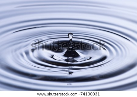 Water drop hitting the clean surface of the water - stock photo