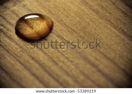 Water drop on a wooden surface. - stock photo