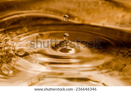 Water drop on golden background - stock photo