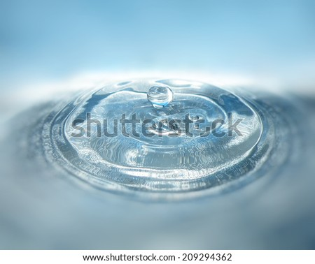 Water drop or bubble falling into water surface and making a crown. Splash background. - stock photo