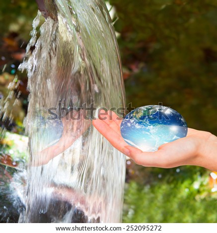 """Water drop shape in the hand ( drinking water crisis) """"Elements of this image furnished by NASA """"  - stock photo"""