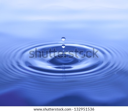 Water Drop Splash on Blue Background with Ripples - stock photo