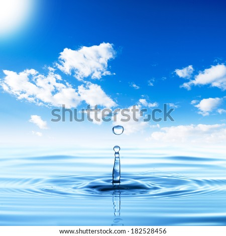 Water droplet with water wave on blue sky - stock photo