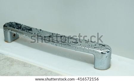 Water Droplets on bathtub handle, soft focus - stock photo