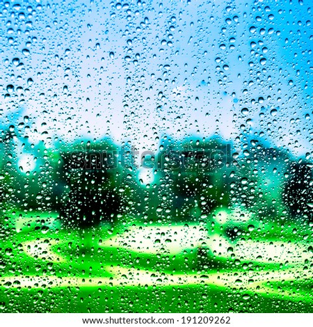Water droplets on glass with Grass background. Raindrops. - stock photo