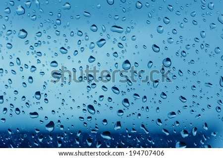 Water droplets on the glass with a colored background. Drops of water.
