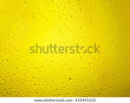 Water droplets on the glass with a Yellow illumination - stock photo
