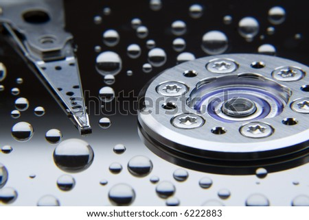 water droplets on the reflective surface of a hard disk with read/write head, macro