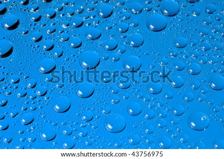 Water droplets with catchlights on blue background.