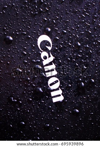 Water drops close-up on a photographic equipment logo CANON