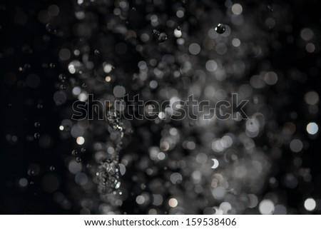 Water drops levitating in the air in dark - stock photo
