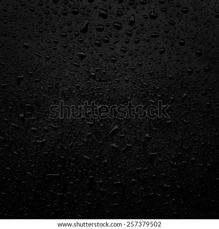 water drops on a black surface - stock photo