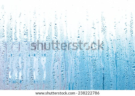 water drops on a window - serenity blue pastel tones - stock photo
