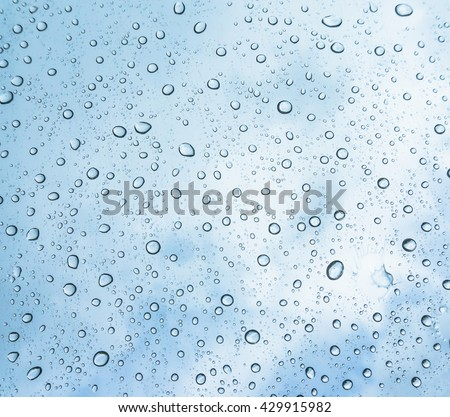 water drops on blue background / Drops of rain on glass , rain drops on clear window / Blue Abstract Water Drops Background / water drops on glass surface as background. - stock photo
