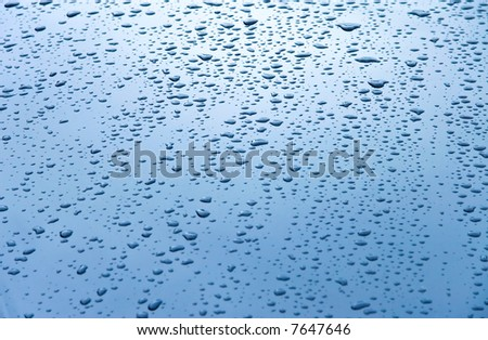 Water drops on car hood. Blue tint. - stock photo