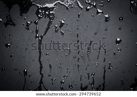 Water drops on dark stone surface of basalt or granite - stock photo