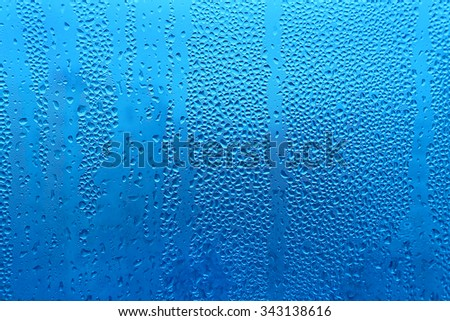 Water drops on glass naural blue texture - stock photo