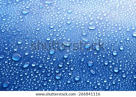 Water drops on glass on blue background - stock photo