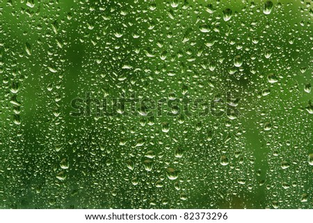 Water drops on glass on green background - stock photo