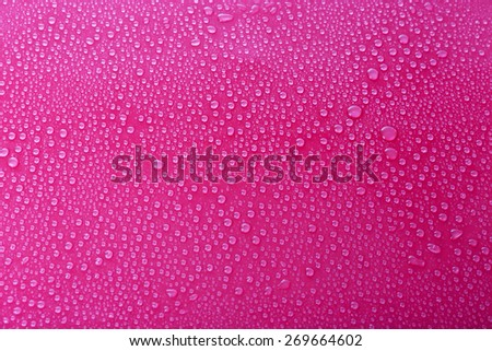 Water drops on glass on pink background - stock photo