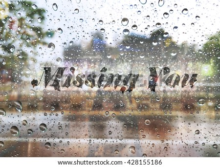 water drops on glass window with text missing you in raining Season - stock photo
