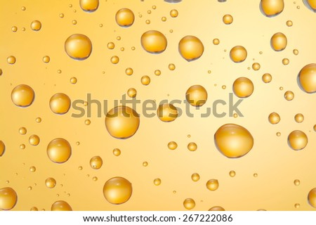 Water drops on glass with orange lighting.