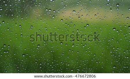 Water drops on green transparent glass close up