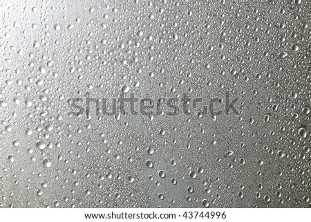 water drops on silver metal surface - stock photo